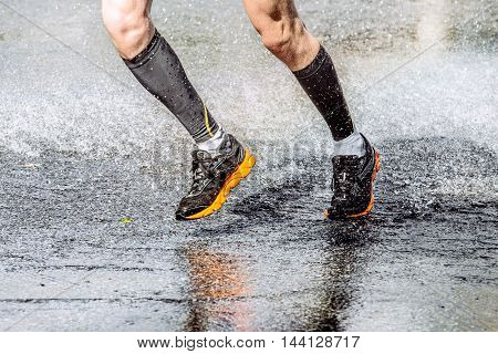 athlete foot men running through a puddle spray and water drops during a sports race