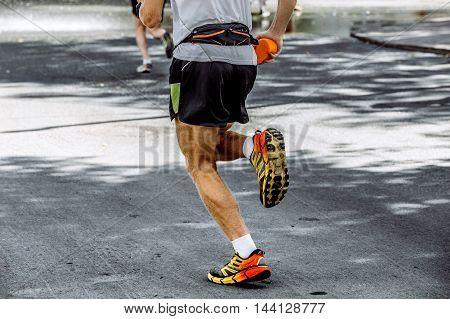 male athlete running marathon in hand sponge with water