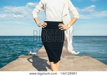 Elegant Business Woman In A Skirt And Cardigan On A Background Of The Sea On A Sunny Day