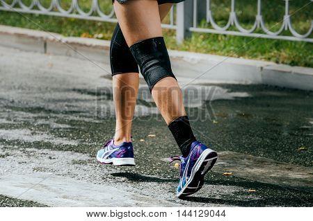 legs women athletes in knee pad running sports race around city