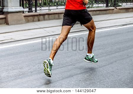 side view of legs of male athlete running sports race