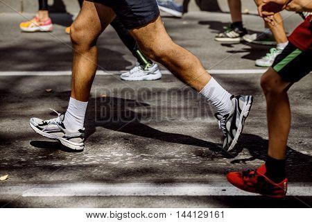 feet group of athletes running marathon on city street