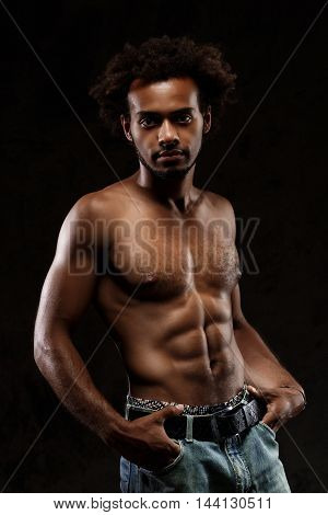 Young sportive african handsome  man posing over black background. Copy space.