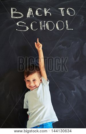 Smiling first grader is pointing at the chalk inscription on the blackboard in class