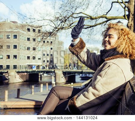 cute pretty mulatto woman waving and smiling welcoming friends, streets of Amsterdam, lifestyle people concept