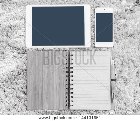 Closeup brown note book with line in page brown pen tablet and smart phone on gray fabric capet textured background in top view in work concept in black and white tone