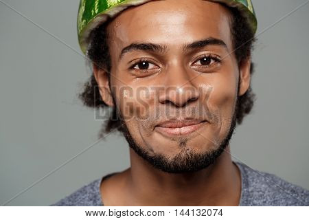 Young handsome frican man with watermelon on head fooling over grey background. Copy space.