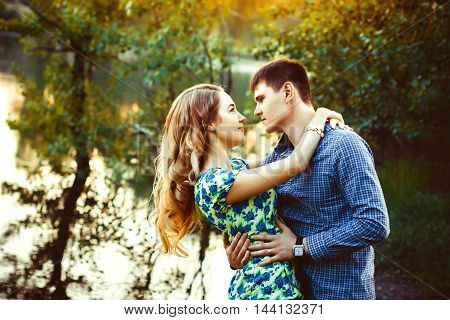 A loving couple looking at each other in the last rays of the sun in a forest near the lake.