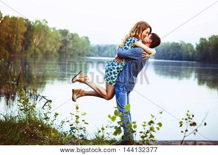 A loving couple hugging and kissing by the lake. The girl picks up a guy in the air.