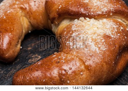 The tasty croissant on dark wooden background