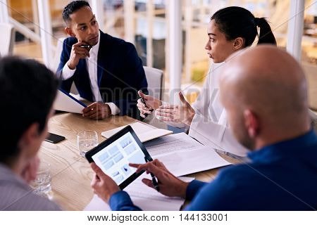 Diverse group of four business individuals listening to a young female partner busy talking to them while looking up the figures she is referring to on his electronic tablet in real time.