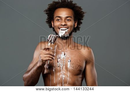Young handsome african man eating icecream, posing over grey background. Copy space.