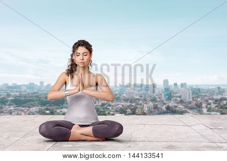 Yoga and meditation in a modern city. Young woman doing yoga on the roof