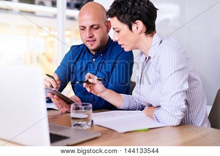 Caucasian male and female business partners working together in the conference room of their new modern offices where they are discussing expansion plans.