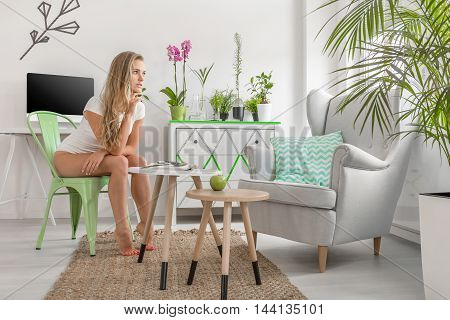 Young woman sitting on a chair in new design light flat interior decorated with green houseplants