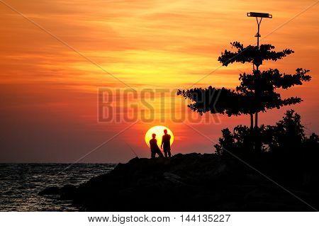 Silhouette of people enjoying beautiful sunset at Labuan Pearl Of Borneo,Malaysia.
