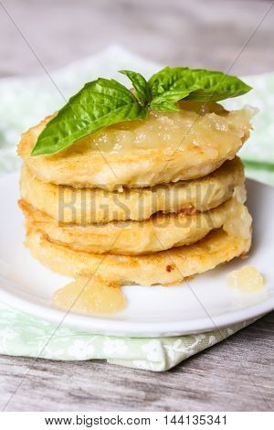 Stack of potato pancakes or fritters with apple sauce and fresh basil leaves on a plate, selective focus