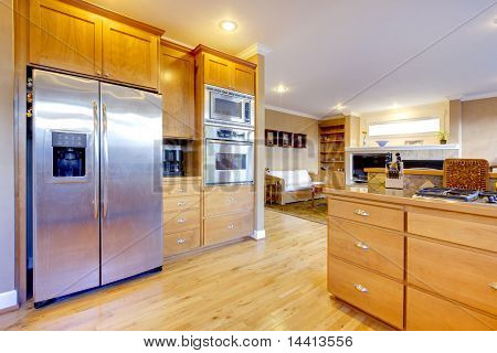 Large Kitchen With Maple Cabinets And Large Refrigirator.