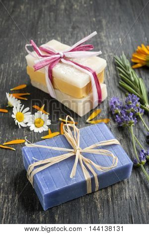 Colorful handmade soaps with fresh herbs on rustic wooden background