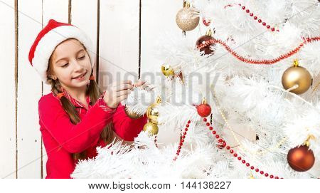 little cute girl in red santa hat decorating new year tree