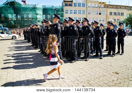 Uzhgorod Ukraine - August 25. 2016: Girl passes near the policemans during the ceremony of awarding titles to inspectors of police officers .