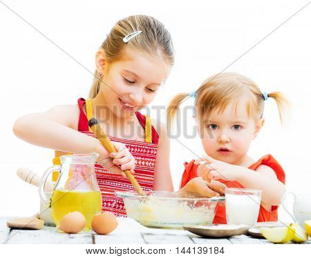 two little sisters baking isolated on a white background