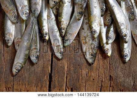 Salted anchovies fish on wooden table, close up