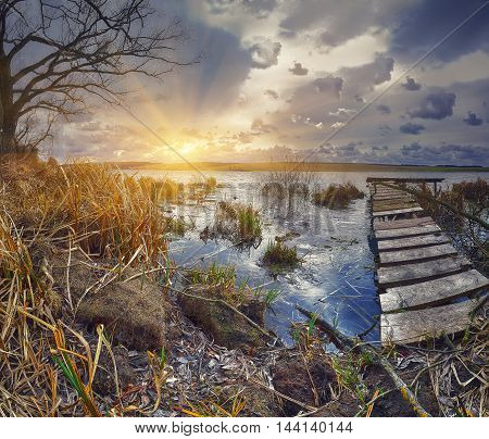 Old wooden pier with dry reed on sunset. Cloudy weather. Dramatic sky