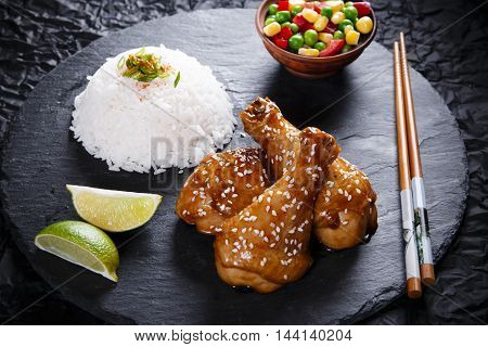 Fried chicken legs with teriyaki sauce sesame seeds and rice on black stone