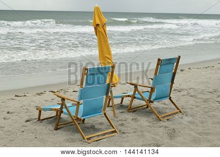 Pair of wooden beach chairs and umbrella on Cocoa Beach, Florida.