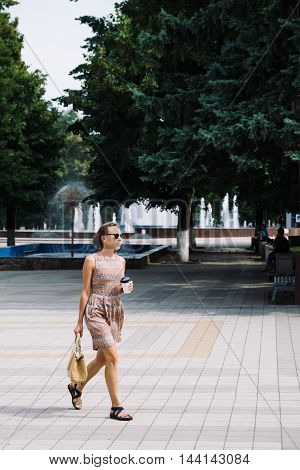 Portrait of young woman in dress and sunglasses walking against of fountains in park with coffee to go