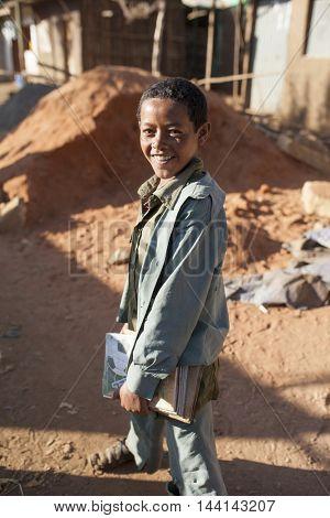 OROMIA, ETHIOPIA-NOVEMBER 6, 2014: Unidentified student carries his books in a rural village in Oromia, Ethiopia