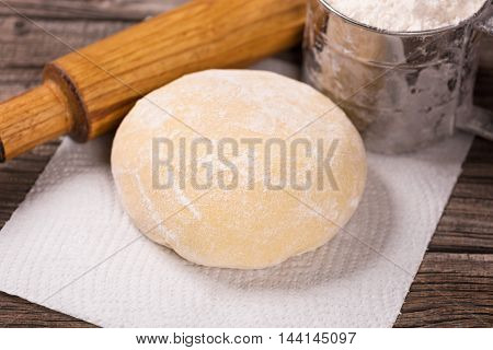 Soft dough with rolling pin and flour over wooden surface background