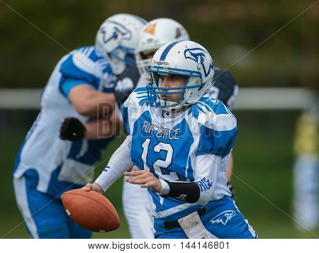 TULLN, AUSTRIA - APRIL 26, 2015: QB Oliver Schreiner (#12 Hawks) runs with the ball in a game of the Division IV of the Austrian Football League.