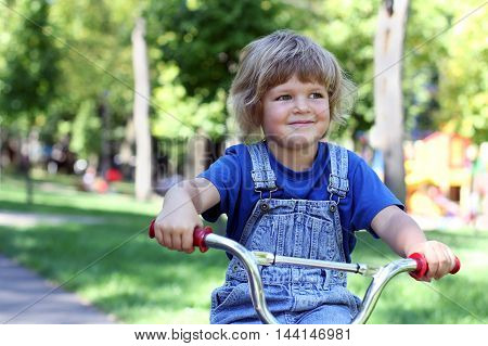beautiful little blonde girl in denim overalls rides a bike in the park