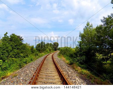 Railroad in nature and partly cloudy sky