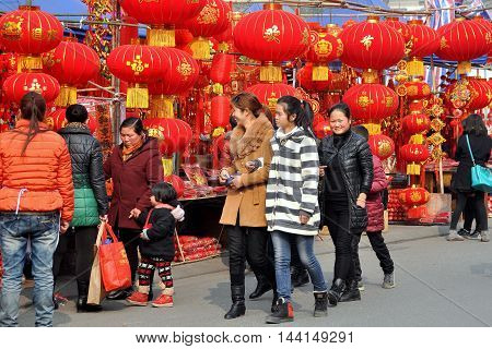 Pengzhou China - January 23 2014: People shopping for Chinese Lunar New Year decorations at the Long Xing outdoor marketplace