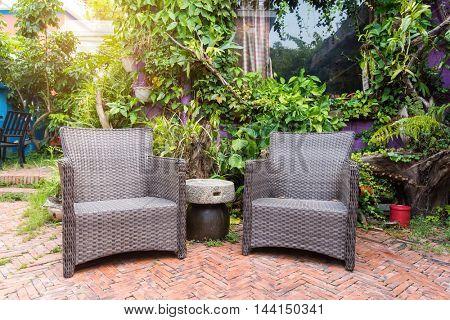 Cozy wickers chair in beautiful flourishing garden