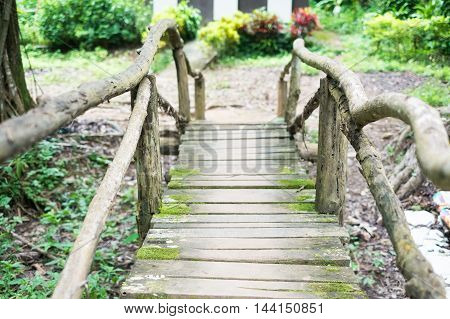 Old wooden bridge with moss across a river