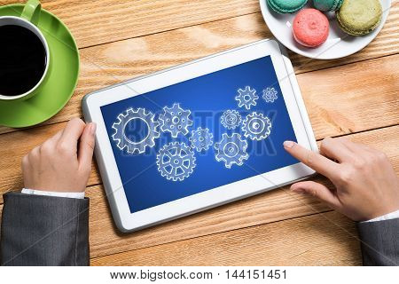 Top view of businesswoman sitting at table and using tablet