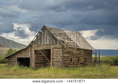 old, rustic, log barn in Colorado's Rocky Mountains with a stormy sky