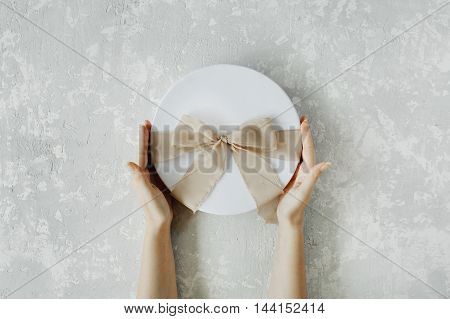 white gift cardboard box with brown bow and girl's hands on concrete background. flat lat top view