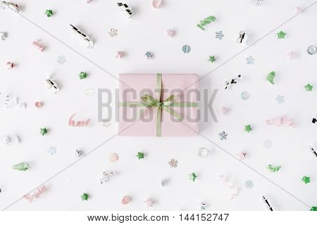pink gift box with ribbon and bow on white decorated with tinsel background. flat lat top view