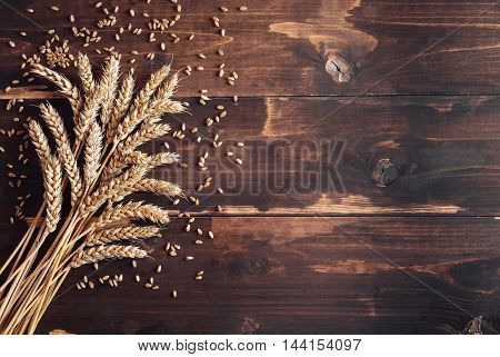 Ripe golden wheat on distressed wooden rustic background, copy space, harvest concept