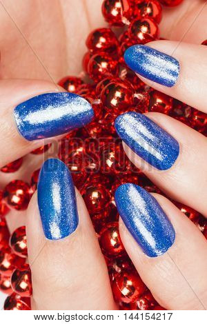 Female hand with blue nails holds red pearls.