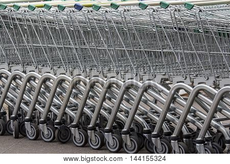 Metal grocery cart on wheels on the car Parking
