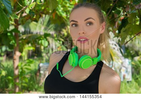 Close up of young pretty fitness female wearing bright green headphones standing under tropical green palm trees and enjoying beautiful summer day