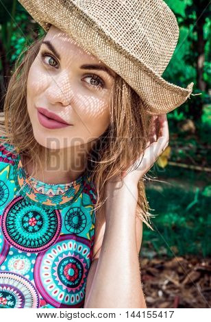Portrait of beautiful woman in bikini and straw hat on a sunny day smiling and looking into camera over palm trees background. Face closeup of pretty girl with straw hat pattern shadow on her face