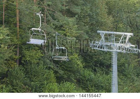 Poland Pieniny mountains Szczawnica Palenica chairlift tower quad chairs passengers woods in the background summer