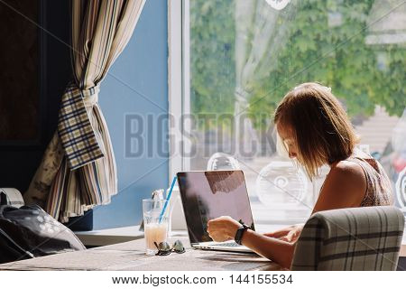 Side view of young short-haired woman in dress using laptop while sitting at table with drink and tablet in cafe against of window